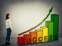 Career stairway graph. Smiling businesswoman standing in front of a rising graph as a staicase with a arrow going up. Ambitions concept, stairway of successful Stock Photo