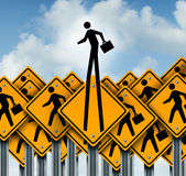 Career Success. And climb to the top concept as a group of worker crossing traffic signs with one businessman icon breaking out  from the pack as a symbol of Royalty Free Stock Photos