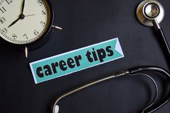 Career Tips on the paper with Healthcare Concept Inspiration. alarm clock, Black stethoscope. royalty free stock image