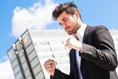 Career of young worker man. Business man. A young businessman with hands closed in a fist. Behind him, an office building and blue sky. Business, career, youth stock photography