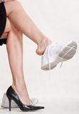 Careerwoman working legs. Changing shoes from heels to runners Royalty Free Stock Photo