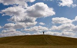 Carefree. Man with outstreched hands on top of small hill Stock Photography