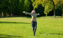 Carefree adorable girl with arms out in field. Royalty Free Stock Photography