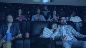 Carefree adults watching film in modern cinema holding drinks and snacks. Sitting in comfortable chairs looking at screen. People, culture and leisure time stock video