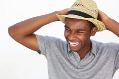 Carefree african american man smiling with hat. Close up portrait of a carefree african american man smiling with hat on white background Royalty Free Stock Image