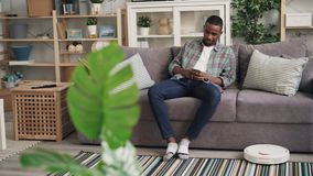 Carefree African American man is using robotic vacuum cleaner sitting on sofa and holding smartphone enjoying