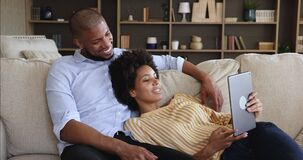 Carefree African couple spend lazy weekend use digital tablet