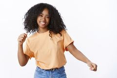 Carefree attractive happy young african-american curly-haired girl wearing spring orange t-shirt dancing waving hands stock photography