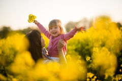 Carefree baby and mother on nature in rapeseed field Royalty Free Stock Image