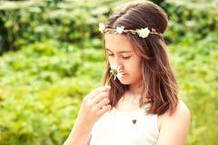Carefree barndom Flicka med fjärilen som luktar kamomill royaltyfria foton