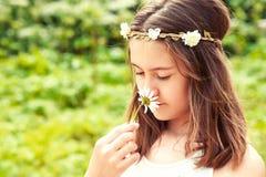Carefree barndom Flicka med fjärilen som luktar kamomill arkivbilder