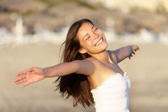 Carefree beach woman happy. And serene smiling on beach at sunset. Joyful beautiful young mixed race Asian / Caucasian woman portrait stock images