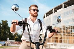 Carefree bearded man in sunglasses with backpack Stock Images