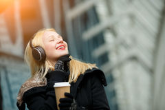 Carefree beautiful young woman enjoying music and hot coffee outdoors. Image with lens flare effect Royalty Free Stock Photography
