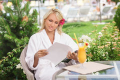 Carefree beauty. Attractive young women in bathrobe reading the Stock Photo