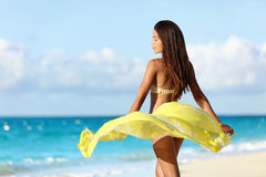 Carefree bikini woman relaxing in beach pareo. Carefree beautiful sexy bikini body woman relaxing in yellow flowing cover-up beachwear fashion wrap on ocean Stock Photo