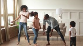 Carefree black parents and kids dancing together in living room