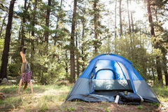 Carefree blonde camper doing handstand next to tent Stock Photos