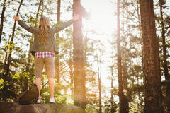 Carefree blonde hiker standing on stone with arms outstretched Royalty Free Stock Photos