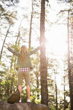 Carefree blonde hiker standing on stone with arms outstretched Royalty Free Stock Photo