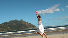 Carefree blonde running on the beach holding scarf up. In slow motion stock video footage