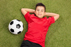 Carefree boy in a red football jersey lying on grass. Carefree little boy in a red football jersey lying on grass with a ball next to him Royalty Free Stock Photo