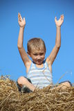 Carefree boy resting in haystack Stock Images