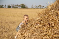 Carefree boy resting in haystack Royalty Free Stock Photos