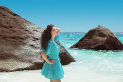 Carefree brunette woman in blue dress enjoying life near seashore in tropical beach with rocks. Enjoyment. Lifestyle. Freedom. royalty free stock image