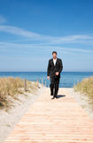 Carefree business success career. Carefree successful businessman walking with success on boardwalk on coastline with blue sky and sea wearing tie and formal Royalty Free Stock Photos
