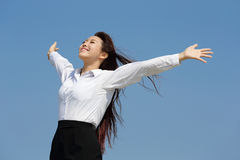 Carefree business woman. Arms up and feel free isolated on blue sky background, asian beauty stock photo