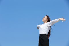 Carefree business woman. Arms up and feel free isolated on blue sky background, asian beauty stock photography