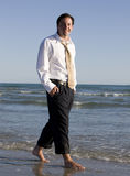 Carefree Businessman. A young businessman in work slacks, shirt and tie casually walks along an ocean beach Royalty Free Stock Photography