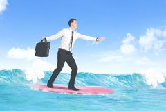 Carefree caucasian businessman surfing. Carefree businessman enjoying freedom surfing at sea Royalty Free Stock Photo