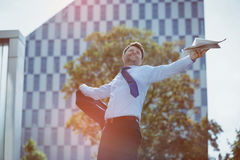 Carefree businessman holding blazer and newspaper. Near office building Royalty Free Stock Photos