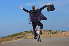 Carefree businessman holding a briefcase. And riding a bicycle outdoors Royalty Free Stock Photography