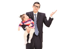 Carefree businessman holding his daughter. And gesturing with his hand isolated on white background Royalty Free Stock Photography