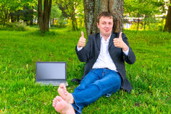 Carefree businessman in the park. Shows all good Stock Photography