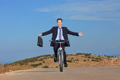 Carefree businessman riding a bicycle. Carefree businessman holding a briefcase and riding a bicycle outdoors Royalty Free Stock Image