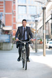 Carefree businessman riding a bicycle outdoors. Go to work Royalty Free Stock Image