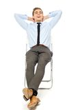 Carefree businessman sitting. Young man over white background Royalty Free Stock Images