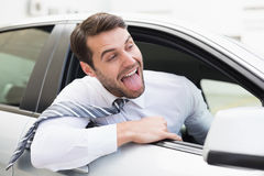 Carefree businessman sitting in drivers seat. In his car Royalty Free Stock Photos