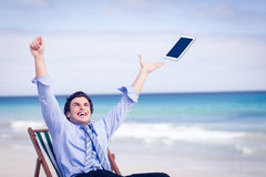 Carefree businessman throwing up his tablet in the air Stock Photos