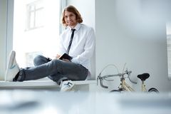 Carefree businessman. Young businessman sitting on window-sill in snickers Stock Image