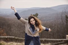 Carefree candid portrait, arms extended, young Caucasian woman girl outdoors. Wilderness, looking away, forest mountain Royalty Free Stock Images