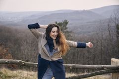 Carefree candid portrait, arms extended, young Caucasian woman girl. Outdoors wilderness, forest mountain Royalty Free Stock Photo