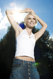Carefree casual woman in a summer sunburst. Carefree beautiful casual young blond woman in a summer clothes with a sunburst alongside her head smiling in Stock Photography