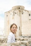 Carefree Caucasian girl making faces. Playful and carefree cute little Caucasian girl making faces, looking at mum and dad Stock Photo