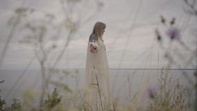 Carefree caucasian woman wearing long summer fashion dress standing on the field on the background of a lake or river. Rear view at awe caucasian woman wearing stock video footage