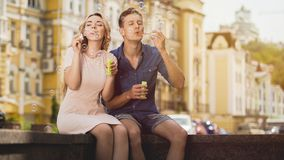 Carefree cheerful couple blowing bubbles, enjoying freedom and youth, love. Stock video Royalty Free Stock Images